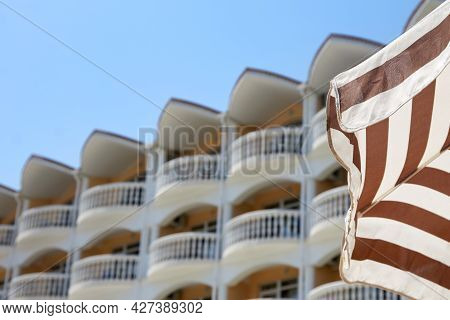 Striped Sun Umbrella On The Background Of The Blue Sky And A Beautiful Hotel. Concept Of Summer Hote