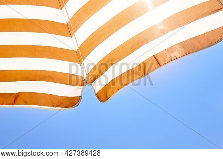 Striped Sun Umbrella Against The Blue Sky. Concept Of Summer Hotel Holidays, Beach Holidays, Tanning
