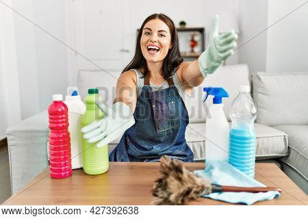Young brunette woman wearing cleaner apron and gloves cleaning at home looking at the camera smiling with open arms for hug. cheerful expression embracing happiness.