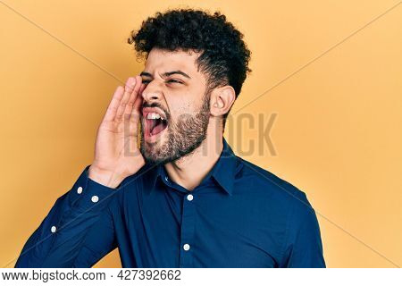 Young arab man with beard wearing casual shirt shouting and screaming loud to side with hand on mouth. communication concept.