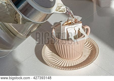 Drip Brewing Coffee. Pouring Hot Water Into Cup With Drip Coffee Bag On White Marble Table, Closeup