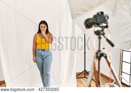 Young beautiful hispanic woman posing as model at photography studio feeling unwell and coughing as symptom for cold or bronchitis. health care concept.