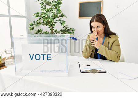 Young brunette woman sitting at election table with voting ballot smelling something stinky and disgusting, intolerable smell, holding breath with fingers on nose. bad smell