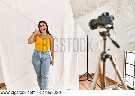 Young beautiful hispanic woman posing as model at photography studio smiling doing phone gesture with hand and fingers like talking on the telephone. communicating concepts.