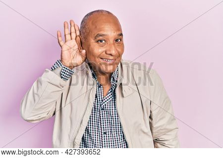 Middle age latin man wearing casual clothes smiling with hand over ear listening and hearing to rumor or gossip. deafness concept.