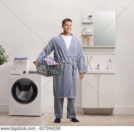 Full length portrait of a young man in a bathrobe holding a laundry basket in a bathroom