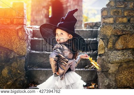 Emotional Little Girl With A Yellow Leaf In Hand, In A Witch Hat Walks Through The Stone Castle, Loo