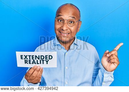 Middle age latin man holding paper with extended reality message smiling happy pointing with hand and finger to the side