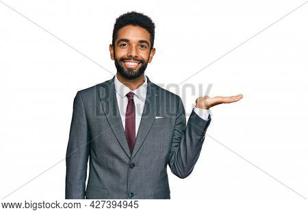 Young african american man wearing business clothes smiling cheerful presenting and pointing with palm of hand looking at the camera.