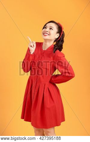 Full Length Of Flirtatious Woman With Radiant Smile Wearing Red Dress With Hand On Hip Isolated On Y