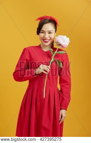 Stylish Girl In White Floral Shirt Gently Holding Peony Flower In Hands