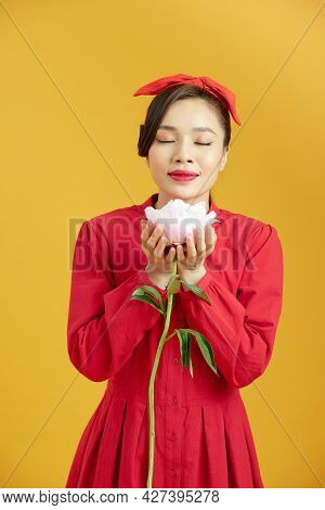 Portrait Of Adorable Young Woman Standing With Charming Smile, Holding Peony Flower In Hands And Sme