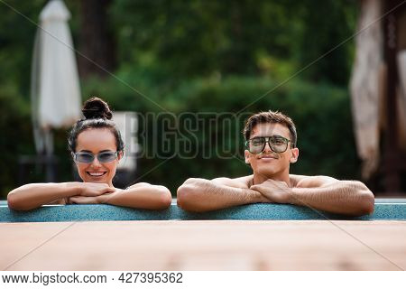 Smiling Couple Looking At Camera Near Poolside On Resort