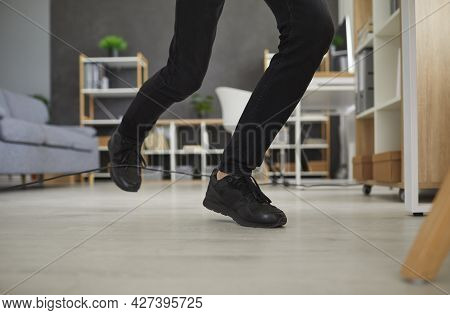 Closeup Shot Of Feet Of A Man Who Trips Over An Electric Cord At Home Or In The Office