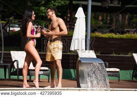 Side View Of Shirtless Man Talking To Girlfriend With Orange Juice Near Swimming Pool