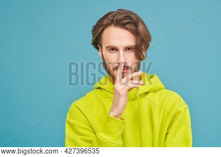 People, emotions. Handsome young man in bright light green hoodie looking at the camera. Photographer, cameraman. Studio portrait on a blue background with copy space.