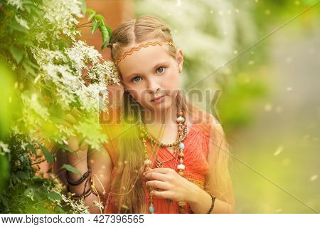 Portrait of a cute girl child dressed in hippie style stands next to flowering shrubs along the fence. Romantic hippie style.