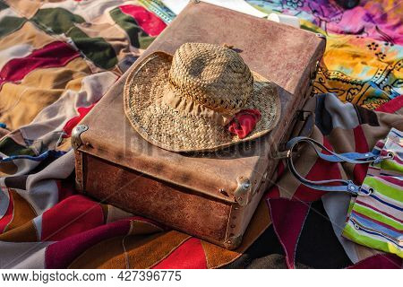 Old Straw Hat On Vintage Suitcase And Colored Blanket On Sunny Summer Day, Concept Of Trip To Nature