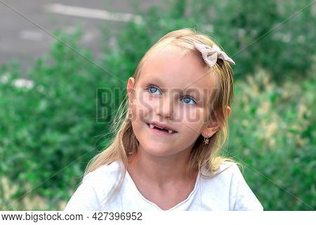 Girl 6 Years Old, Blonde, Blue Eyes, Smiling, And There Are No Milk Teeth In Her Mouth, Portrait Of