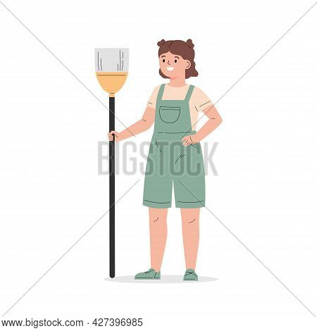 Young Girl Dressed In Overalls With A Broom. The Girl Helps With The Household. Child Cleaning. Flat