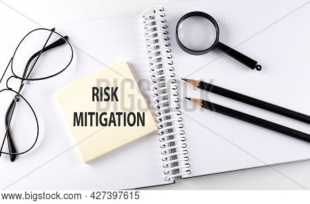 Text Risk Mitigation On Sticker With Keyboard , Pencils And Office Tools