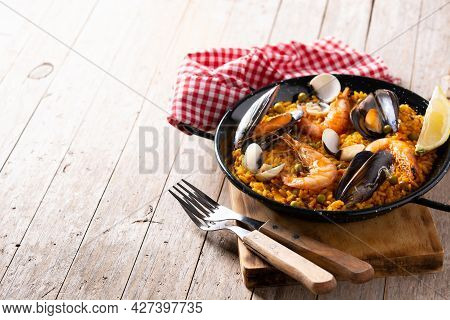 Traditional Spanish Seafood Paella On Wooden Table. Copy Space