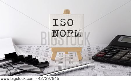 Text Iso Norm On Easel With Office Tools And Paper.top View. Business