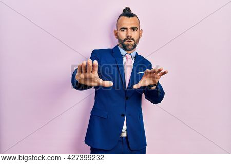 Young hispanic man wearing business suit and tie doing stop gesture with hands palms, angry and frustration expression