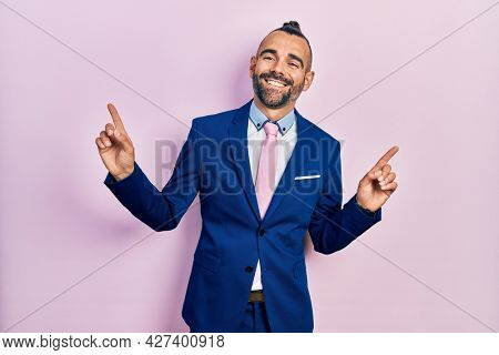 Young hispanic man wearing business suit and tie smiling confident pointing with fingers to different directions. copy space for advertisement