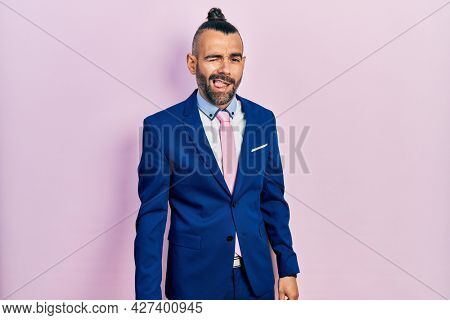 Young hispanic man wearing business suit and tie winking looking at the camera with sexy expression, cheerful and happy face.