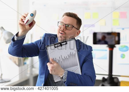 Emotional Male Blogger Holds Rocket In Hand And Conducts Online Training On Quick Start In Business