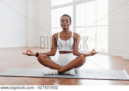 Young Black Woman Sitting In Lotus Position On Mat, Meditating