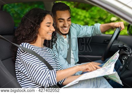 Happy Middle-eastern Couple Sitting In Car, Planning Journey