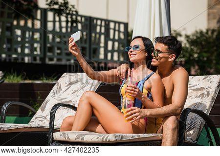 Young Shirtless Man Hugging Girlfriend With Orange Juice Taking Selfie On Deck Chair