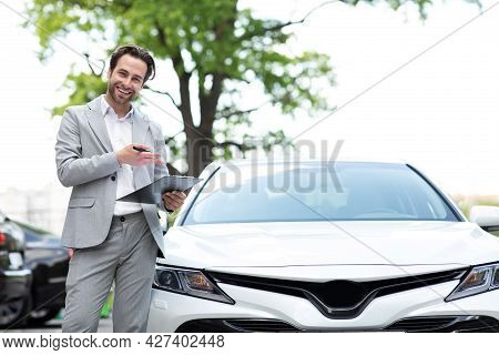 Handsome Car Dealership Worker In Suit, Holding Folder And Smiling, Standing Near Auto