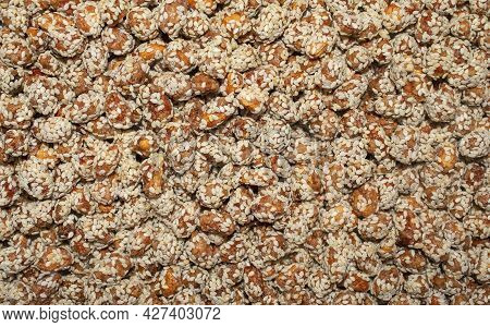 Background Made Of Peanuts Or Raisins Covered With Brown Caramel And Sesame Seeds. Carameled Nuts
