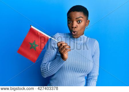 Young african american woman holding morocco flag scared and amazed with open mouth for surprise, disbelief face