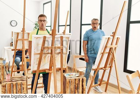 Group of middle age people artist at art studio scared and amazed with open mouth for surprise, disbelief face
