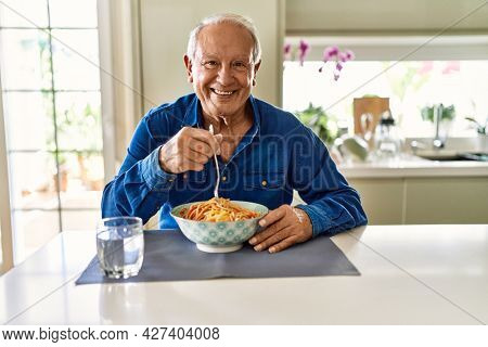 Senior man with grey hair eating pasta spaghetti at home with a happy and cool smile on face. lucky person.