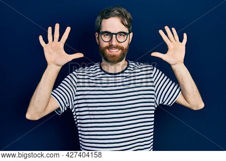 Caucasian man with beard wearing striped t shirt and glasses showing and pointing up with fingers number ten while smiling confident and happy.