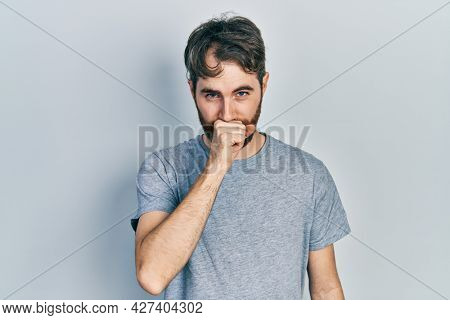 Caucasian man with beard wearing casual grey t shirt feeling unwell and coughing as symptom for cold or bronchitis. health care concept.