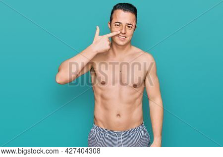 Handsome young man wearing swimwear shirtless pointing with hand finger to face and nose, smiling cheerful. beauty concept