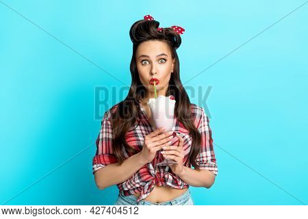 Shocked Young Pinup Woman In Retro Clothes Drinking Yummy Milk Shake On Blue Studio Background