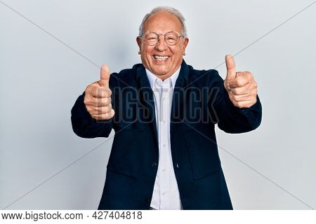 Senior man with grey hair wearing casual style and glasses approving doing positive gesture with hand, thumbs up smiling and happy for success. winner gesture.