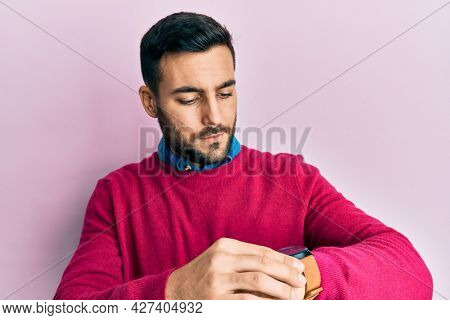 Young hispanic man wearing casual clothes checking the time on wrist watch, relaxed and confident