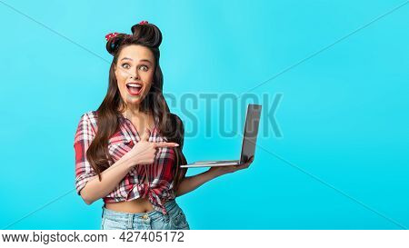 Excited Pinup Woman In Retro Style Wear Pointing At Laptop Computer Over Blue Background, Banner Des