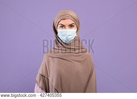Coronavirus Concept. Portrait Of Muslim Lady In Hijab Wearing Protective Mask, Standing Over Purple