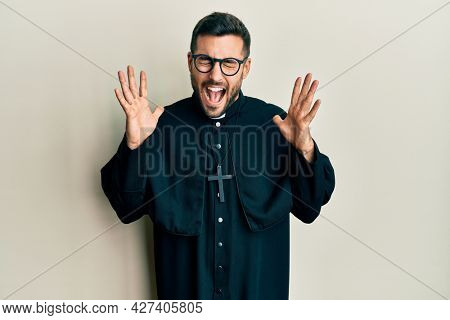 Young hispanic man wearing priest uniform standing over white background celebrating mad and crazy for success with arms raised and closed eyes screaming excited. winner concept