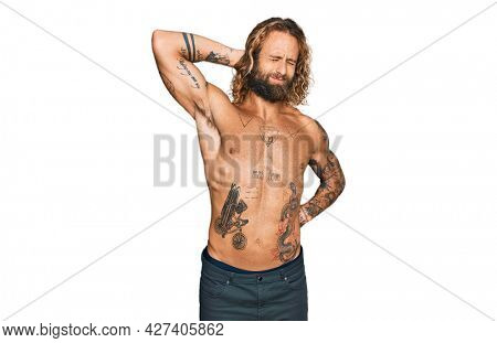 Handsome man with beard and long hair standing shirtless showing tattoos suffering of neck ache injury, touching neck with hand, muscular pain