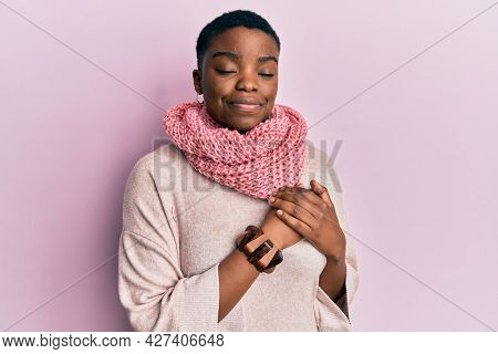 Young african american woman wearing winter scarf smiling with hands on chest with closed eyes and grateful gesture on face. health concept.